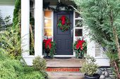 Front door with a Christmas wreath and bows. Merry Christmas stencilled on the front step.  poster