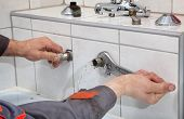 image of leak  - Plumber hands fixing water pipe with spanner and with leaking water from pipe