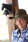Portrait of young country girl in western hat outside of country house, looking at camera, smiling. poster