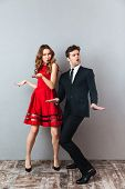 Full length portrait of an attractive happy couple dressed in formal wear dancing together and havin poster