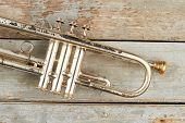 Rusty Trumpet On Wooden Surface. Old Trumpet On Wooden Background. Valve Of Aged Trumpet. Antique Mu poster