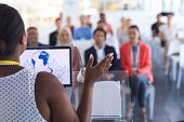 Rear view of pretty African-american female speaker giving speech to diverse people in a business se poster