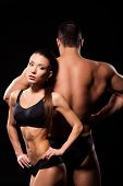 Bodybuilding Couple Posing Back-to-back. Fit Couples Back-to-back Pose. Motivating Each Other. Prepa poster