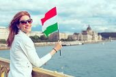 Happy Young Redhead Hungarian Urban Woman Holding Hungarian Flag At Budapest poster