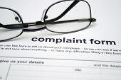 stock photo of moaning  - Close up of reading glasses on Complaint form - JPG