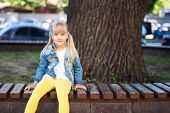 Adorable Blond Caucasian Preschooler Fashionista Girl Wearing Jeans And Bright Yellow Leggins Sittin poster