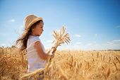 Happy girl walking in golden wheat, enjoying the life in the field. Nature beauty, blue sky and fiel poster