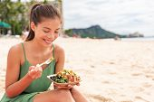 Woman eating poke bowl of ahi tuna on waikiki beach Hawaii. Local food fish salad vacation travel. A poster