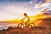Mountain biking cyclist girl riding MTB bike on coast trail against sunset. Silhouetter of woman doi poster