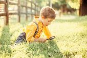 Cute Adorable Caucasian Boy Looking At Plants Grass In Park Through Magnifying Glass. Kid With Loupe poster