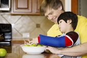 foto of physically handicapped  - Father helping disabled son putting fruit into bowl in the kitchen - JPG