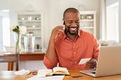 Smiling african man using laptop at home while checking home finance. Happy mature man looking at in poster