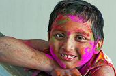 Close Up Face Of Young Boy Playing Holi, Smiling With Colors on face and body