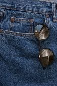Round Sunglasses On A Denim Texture Background. Round Yellow Glasses In The Front Pocket Of Jeans. R poster