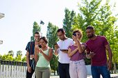 Excited Friends Using Mobile App Outside. Group Of Men And Women Using Smartphones Together And Star poster