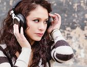 Attractive happy young woman listening to music through head phones.