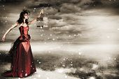 pic of caged  - Beautiful Winter Fashion Woman In Creative Makeup Holding Open Bird Cage On Mountain Landscape In A Depiction Of Freedom - JPG