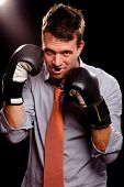 Businessman With Boxing Gloves Guarding His Face. High Contrast.