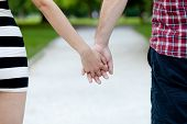 Close Up View Of A Young Couple Holding Hands