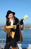 Lovely girl with balalaika is on embankment of Angara River in the city of Irkutsk