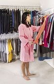 Mature Woman Taking Clothes Off Closet Racks