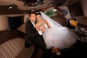 stock photo of fancy-dress  - Romantic young couple sitting in limo on wedding - JPG