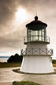 stock photo of mendocino  - Sunlight and stormy skies behind the Mendocino lighthouse - JPG
