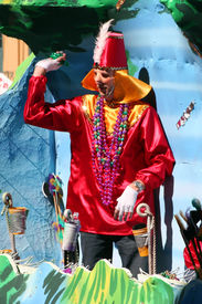 picture of mardi-gras  - a mardi gras parade float rolls through the streets of new orleans during the carnival season while a masked rider in a costume throws beads and doubloons to onlookers below - JPG