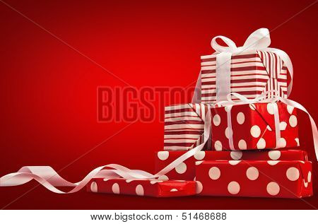 Christmas gifts with ribbon on a red background poster