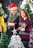 Portrait of young couple holding Christmas presents and shopping bags at store