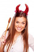 Aggressive beautiful brunette with red devil horns and wooden mixing spoon, isolated on white