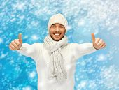 christmas, x-mas, winter, happiness concept - handsome man in warm sweater, hat and scarf showing thumbs up