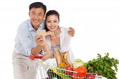 stock photo of woman dragon  - Young couple holding credit cart with vegetable - JPG