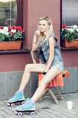 stock photo of roller-derby  - Young pretty woman sitting on the chair - JPG
