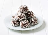 dark chocolate pralines sprinkled with coconut, on a plate