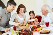 stock photo of grandparent child  - Portrait of happy family sitting at festive table while having Thanksgiving dinner - JPG