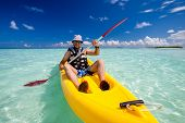 stock photo of canoe boat man  - Caucasian man kayaking in sea at Maldives