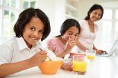 Children Having Breakfast With Mother Before School