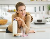 Thoughtful Young Woman With Crisp Bread And Milk In Modern Kitch