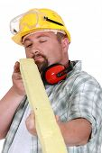 Worker eyeing a piece of wood