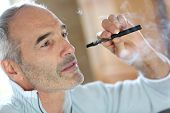 stock photo of smoker  - Portrait of senior smoker with electronic cigarette - JPG