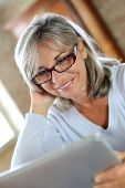 Senior woman with eyeglasses websurfing on internet