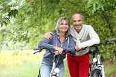 stock photo of bike path  - Cheerful senior couple with bicycle in country path - JPG