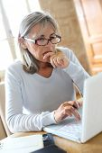 Perplexed senior woman in front of laptop