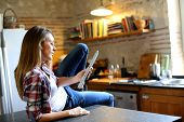 Hipster girl websurfing on tablet in kitchen