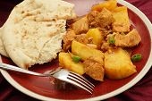 Goan chicken and potato vindaloo curry, cooked in a vinegar and spice sauce and served with a slice