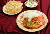 Kashmiri chicken in a serving bowl beside a plate of pappadums and a bowl of raita. The chicken is m