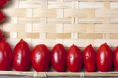 foto of oblong  - Small oblong red ripe tomatoes on a wicker wooden platter - JPG