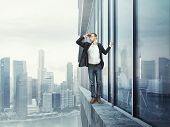 man standing on the edge and looking at the city