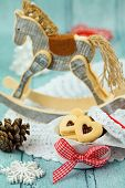 picture of linzer  - Christmas heart shaped linzer jelly cookies with wooden horse at background in vintage style - JPG
